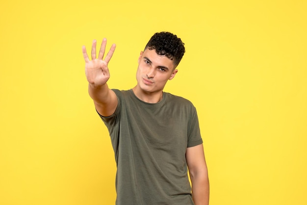 Vooraanzicht van de man toont vier vingers en glimlacht