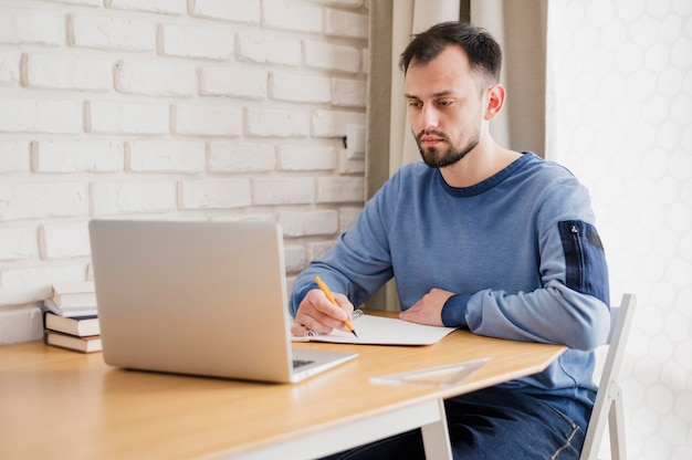 Vooraanzicht van de mens bij bureau dat online van laptop leert