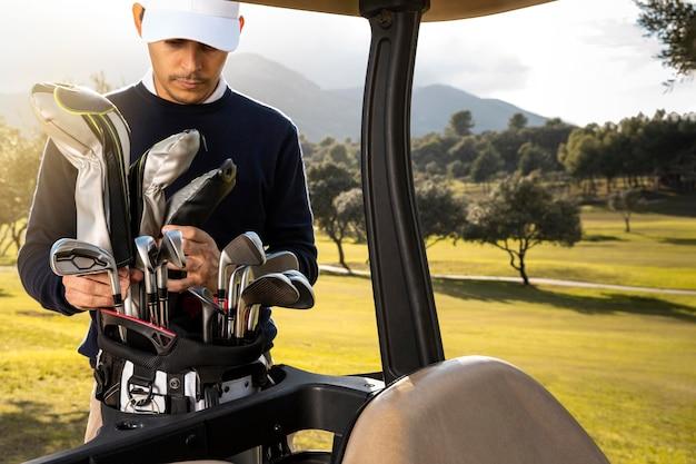 Vooraanzicht van de mens clubs aanbrengend golfkar