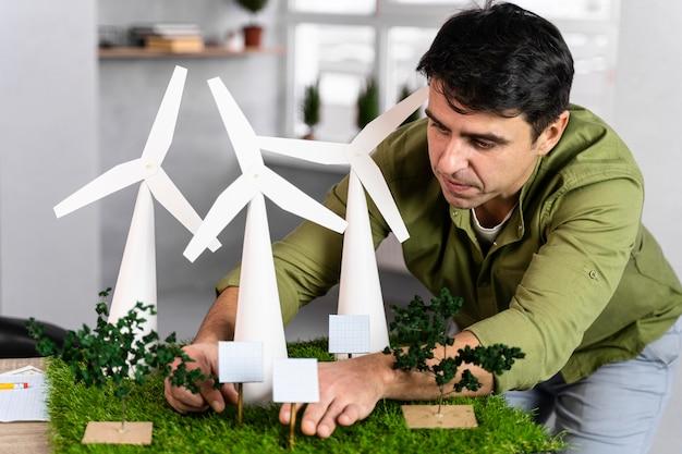 Vooraanzicht van de mens die aan een milieuvriendelijk windenergieproject met windturbines werkt