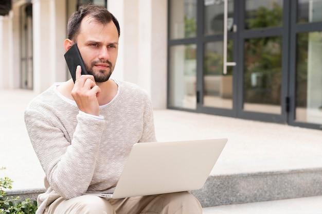 Vooraanzicht van de mens die aan laptop in openlucht werkt