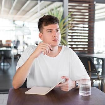Vooraanzicht van de mens die buiten bij pub schrijft