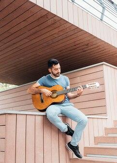 Vooraanzicht van de mens die de gitaar speelt