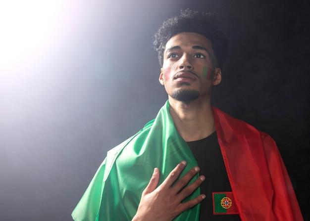 Vooraanzicht van de mens die de vlag van portugal draagt