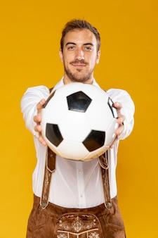 Vooraanzicht van de mens die een bal houdt