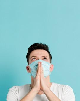 Vooraanzicht van de mens die een medisch masker en het bidden draagt