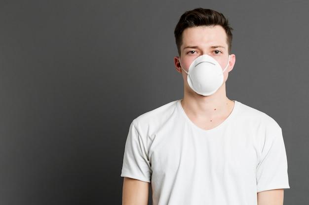 Vooraanzicht van de mens die een medisch masker met exemplaarruimte draagt