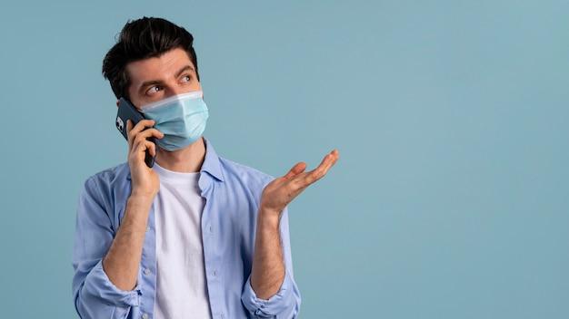 Vooraanzicht van de mens die een telefoongesprek voert terwijl hij een medisch masker draagt