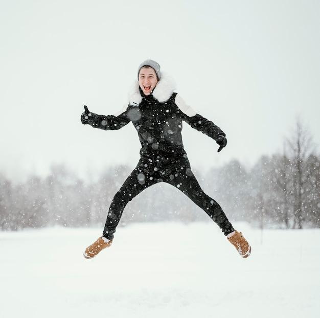 Vooraanzicht van de mens die in de lucht buiten in de winter springt