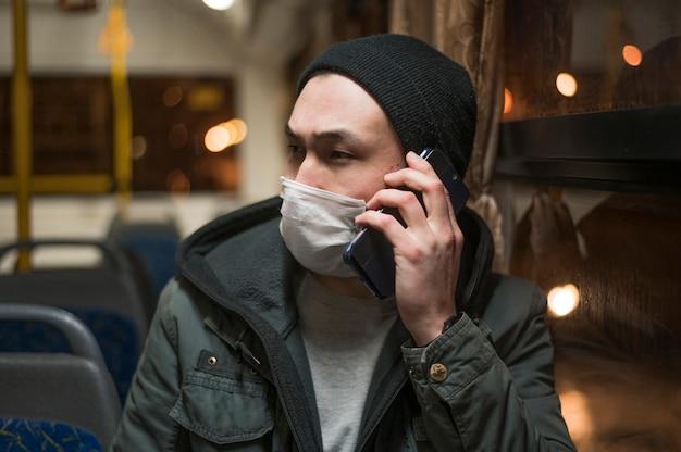 Vooraanzicht van de mens die medisch masker in de bus draagt en op de telefoon spreekt