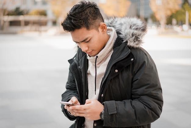 Vooraanzicht van de mens die smartphone buitenshuis gebruikt