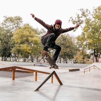 Vooraanzicht van de mens die trucs met skateboard buitenshuis doet