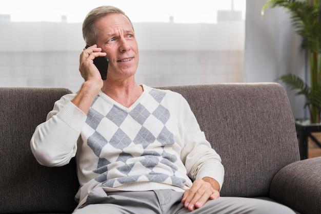 Vooraanzicht van de mens die weg en bij telefoon spreekt spreekt