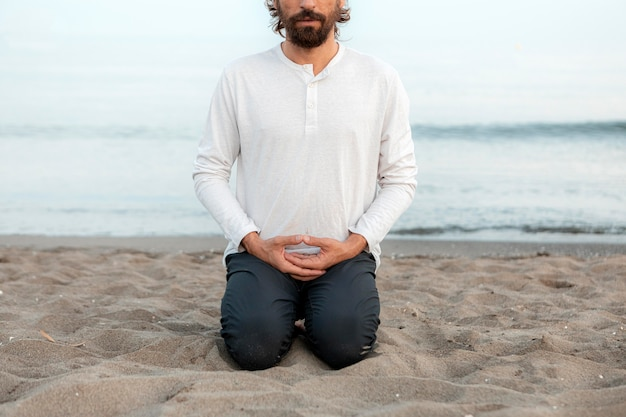 Vooraanzicht van de mens die yoga op het strand doet