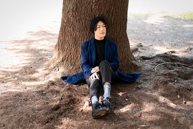 Vooraanzicht van de mens die zich voordeed in het park in de buurt van de boom