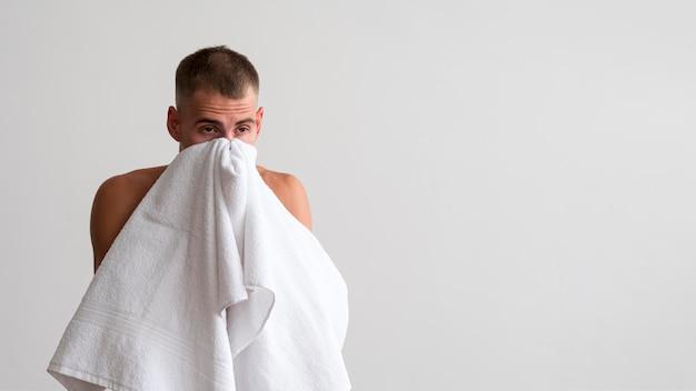 Vooraanzicht van de mens die zijn gezicht met handdoek afveegt na het wassen