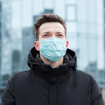 Vooraanzicht van de mens in de stad met medisch masker en jas