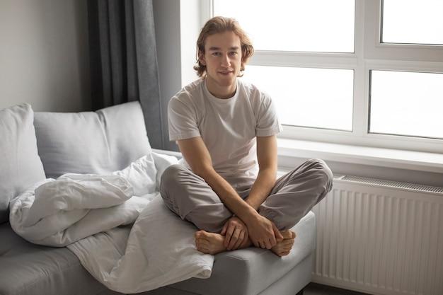 Vooraanzicht van de mens in nachtkleding op sofa