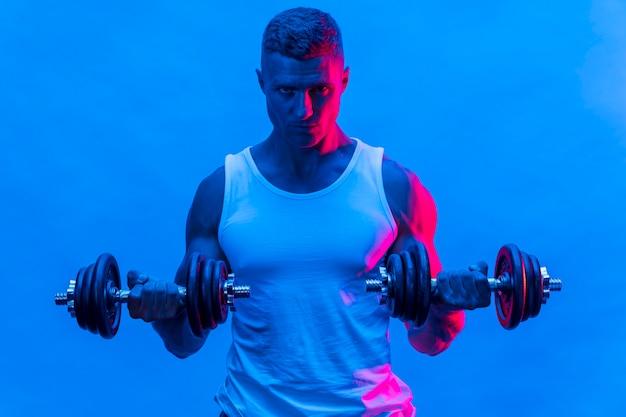 Vooraanzicht van de mens in tanktop die met gewichten oefent