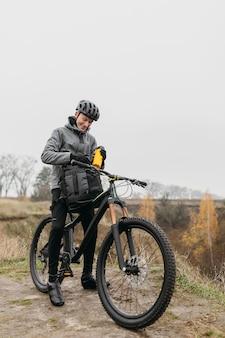 Vooraanzicht van de mens met een fiets in de bergen