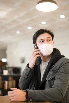 Vooraanzicht van de mens met medisch masker dat op smartphone spreekt