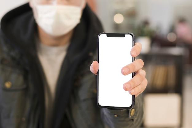 Vooraanzicht van de mens met medisch masker dat telefoon steunt