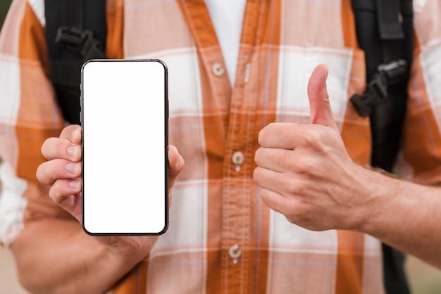 Vooraanzicht van de mens met rugzak die smartphone houdt en duimen opgeeft