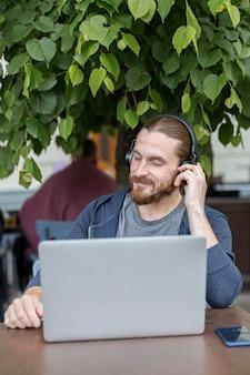 Vooraanzicht van de mens op een terras dat aan muziek op hoofdtelefoons met laptop luistert
