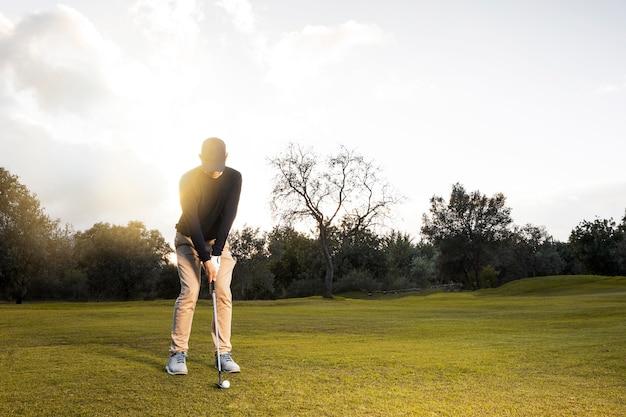Vooraanzicht van de mens op het met gras begroeide golfgebied