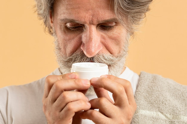 Vooraanzicht van de oudere man met baard ruikende vochtinbrengende crème