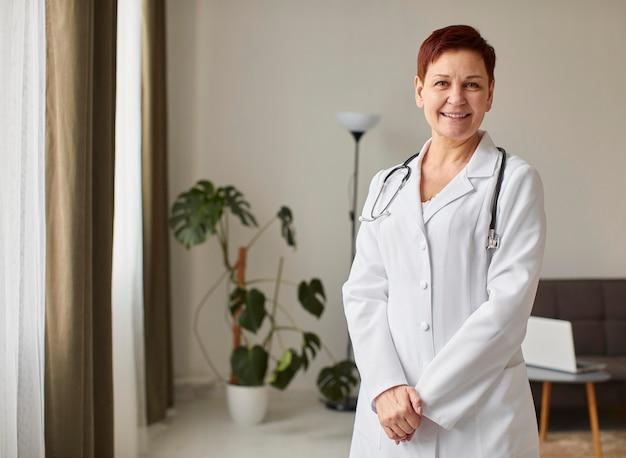 Vooraanzicht van de oudere vrouwelijke arts van het smileycovid herstelcentrum met exemplaarruimte