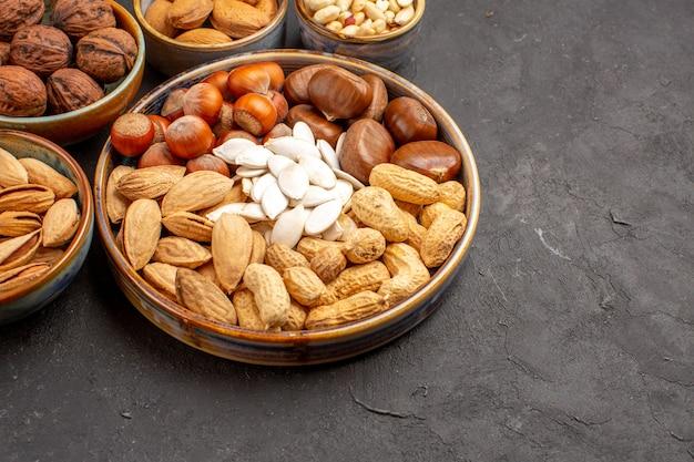 Vooraanzicht van de pinda's van de notensamenstelling en andere noten op donkere oppervlakte