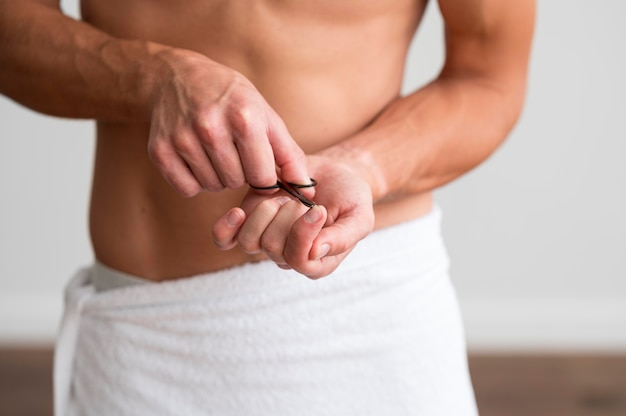 Vooraanzicht van de shirtless man in een handdoek met een schaar op zijn vingernagels