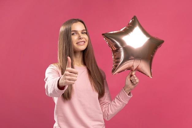 Vooraanzicht van de sterballon van de vrouwenholding en het geven van duimen