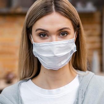 Vooraanzicht van de vrouw bij de salon met medisch masker