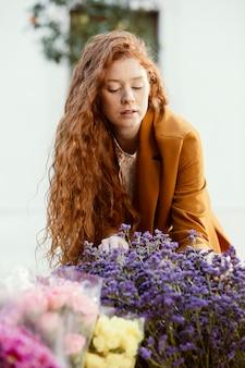 Vooraanzicht van de vrouw buitenshuis met boeket van lentebloemen