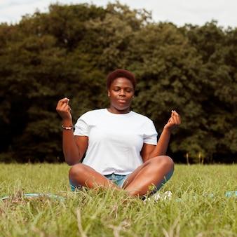 Vooraanzicht van de vrouw die buitenshuis in de natuur mediteert