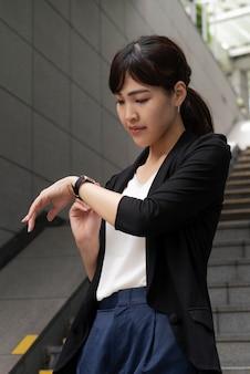 Vooraanzicht van de vrouw die horloge bekijkt
