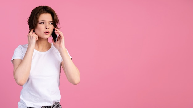 Vooraanzicht van de vrouw die in hard geluid naar haar telefoontje probeert te luisteren