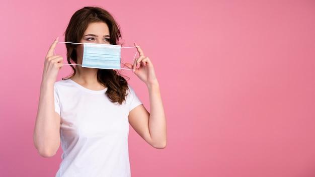 Vooraanzicht van de vrouw die medisch masker opzet