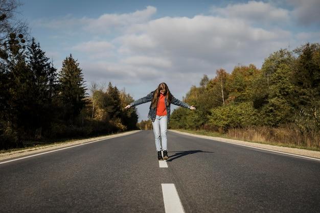 Vooraanzicht van de vrouw die midden op de weg loopt