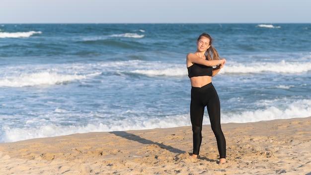 Vooraanzicht van de vrouw die zich uitstrekt voordat u gaat trainen op het strand