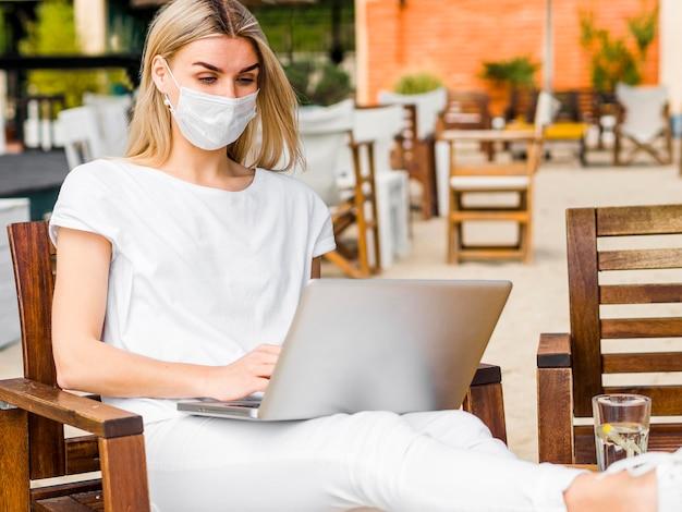 Vooraanzicht van de vrouw in de stoel die op laptop werkt