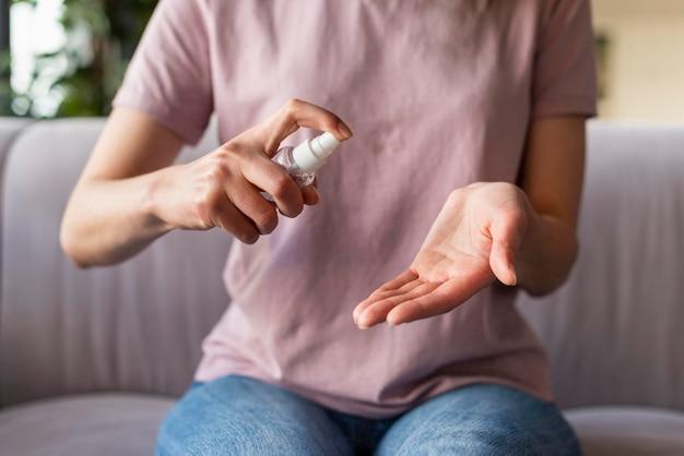 Vooraanzicht van de vrouw met behulp van ontsmettingsmiddelen