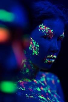 Vooraanzicht van de vrouw met fluorescerende make-up