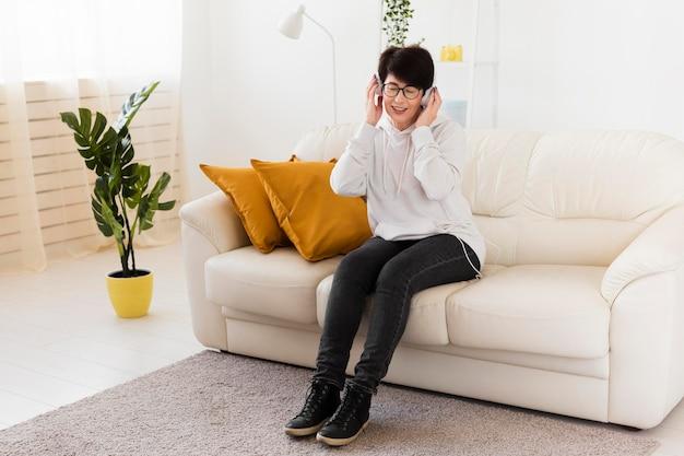 Vooraanzicht van de vrouw op de sofa met een koptelefoon