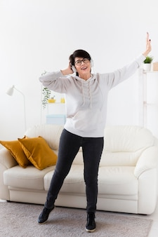 Vooraanzicht van de vrouw thuis met een koptelefoon