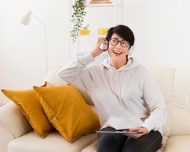 Vooraanzicht van de vrouw thuis met hoofdtelefoons en tablet