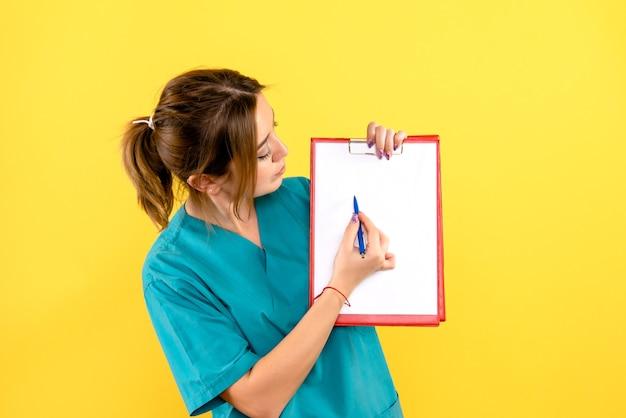Vooraanzicht van de vrouwelijke pen van de dierenartsholding en dossiers op gele muur