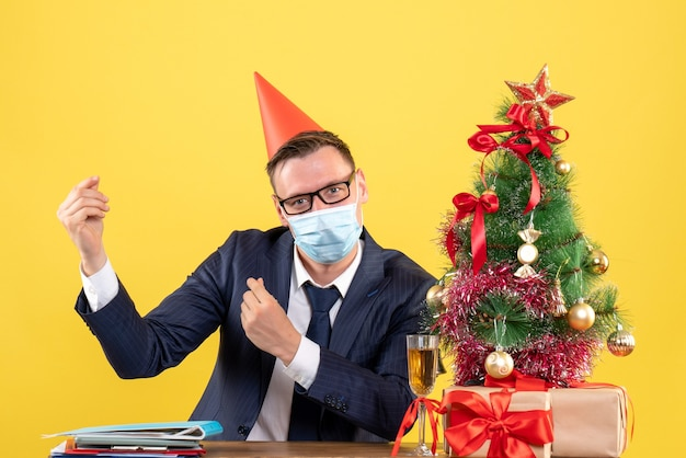 Vooraanzicht van de zakenman die geld maakt teken zittend aan de tafel in de buurt van de kerstboom en presenteert op geel